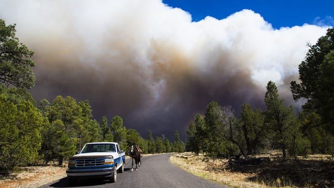 Jack Jacot leads his horse Tonto away from the Tinder Fire on the Mogolon Rim in the Coconino National Forest north of Payson, Ariz. April 29, 2018.