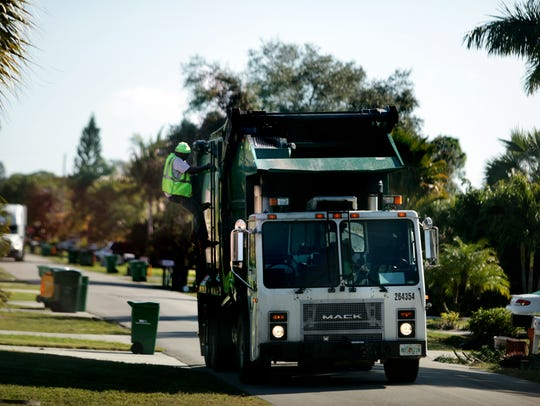 A driver with Waste Management climbs up his truck