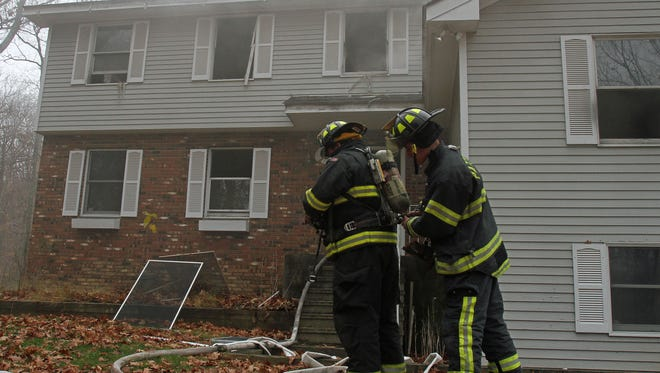 Putnam Lake and Patterson firefighters work at the scene of a house fire at 132 Brimstone Road in Putnam Lake Nov 19, 2015.