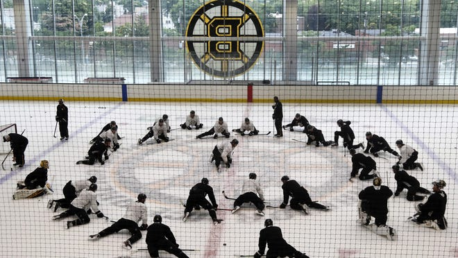 Bruins players stretch before starting their first workout as a team on Monday at Warrior Ice Arena. The NHL has been shut down because of the coronavirus pandemic since mid-March.