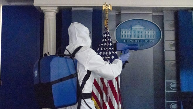 A member of the cleaning staff sprays The James Brady Briefing Room of the White House, Monday, Oct. 5, 2020, in Washington.