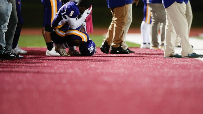 Topeka West sophomore Tyrell Reed takes a knee to wipe his head during Thursday's game against Junction City at Hummer Sports Park. Reed scored West's second touchdown in Thursday's 63-13 loss on a 4-yard run.