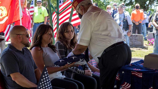 Lisa Hayes is presented with a flag at the funeral service of Vietnam veteran Dennis McKnew.