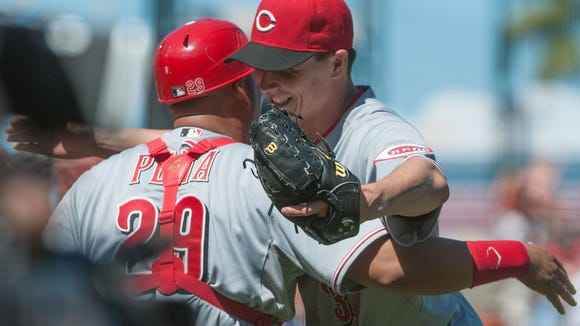 Homer Bailey celebrates with catcher Brayan Pena (29) after defeating the San Francisco Giants.