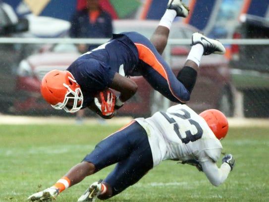 UTEP running back Ronald Awatt, 22, flies over defensive