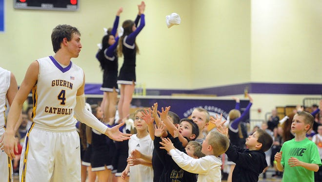 Matt Holba of Guerin flips a souvenir t-shirt to little fans before the start of the game. Guerin Catholic H.S. hosted Pendlton Heights H.S. in a boys basketball game Friday February 21, 2014.