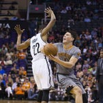 Suns' Devin Booker (1) tries to spin away from Nets' Markel Brown (22) in the first half at Talking Stick Resort Arena in Phoenix, Ariz. on Thursday, February 25, 2016.