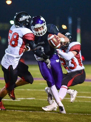 Waukee quarterback Ben Ferkin is sacked by Mason City's Boston Draper (58) and Quinton Jones (23) during the first half of the game at Waukee Stadium on Friday, Oct. 24, 2014.