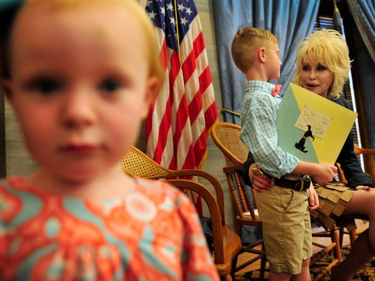 Dolly Parton, right, talks with Dawson Dykes, 6, center, as Dawson's sister Delaney, 2, looks at a camera during a Governor's Books from Birth event in 2014.