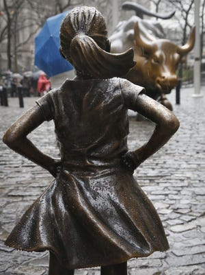 "File photo taken in 2017 shows the ""Fearless Girl"" statue, created by Kristen Visbal, standing near  the ""Charging Bull"" statue, created by Arturo Di Modica."