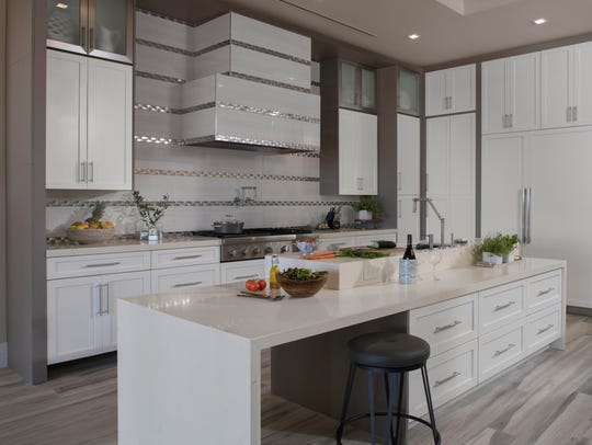 The kitchen features sleek white Shaker cabinetry, complemented by Corian countertops and energy-efficient Thermador appliances.
