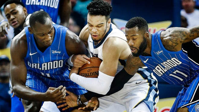 Memphis Grizzlies forward Dillon Brooks (middle) gabs a loose ball away Orlando Magic teammates Bismack Biyombo (left) and Jonathon Simmons (right) during first quarter action at the FedExForum in Memphis, Tenn., Monday, October 2, 2017.