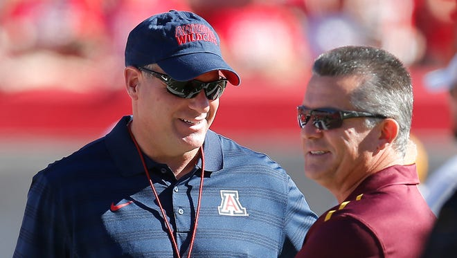 Arizona head coach Rich Rodriguez (left) talks with Arizona State head coach Todd Graham before the Territorial Cup game on Nov. 28 in Tucson.