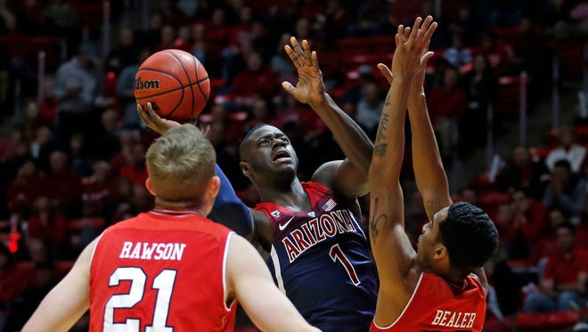 Arizona guard Rawle Alkins (1) shoots as Utah's Tyler Rawson (21) and Gabe Bealer (30) defend in the first half during an NCAA college basketball game Thursday, Jan. 4, 2018, in Salt Lake City. (AP Photo/Rick Bowmer)