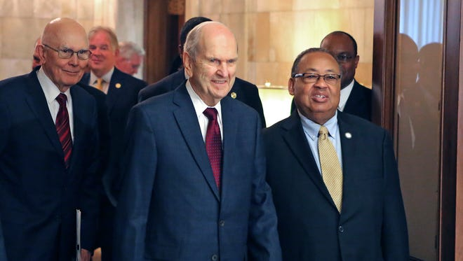 FILE - In this May 17, 2018, file photo, Mormon church President Russell M. Nelson, center, and Leon W. Russell, chairman of the NAACP board of directors, right, walk into a news conference, in Salt Lake City. The Mormon church on Friday, June 1, 2018, will celebrate the 40th anniversary of reversing its ban on black people serving in the lay priesthood, going on missions or getting married in temples, rekindling debate about one of the faith's most sensitive topics. (AP Photo/Rick Bowmer, File)