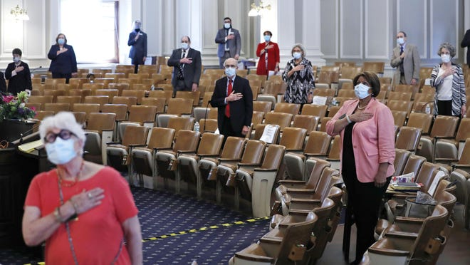 Members of the N.H. Senate stand for the Pledge of Allegience as they gather for a session on Tuesday, June 16, 2020 at the State House in Concord, New Hampshire.  The 24 N.H. Senators met in the N.H. House Chamber to adhere to social distancing rules due to the COVID-19 virus outbreak.