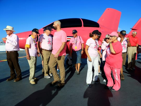 Volunteers from the Lexington Museum on The Bay gather in front of a pink F9F-8 Cougar after it was loaded to the USS Lexington flight deck in support of Breast Cancer Awareness on Oct. 17, 2016, in Corpus Christi.