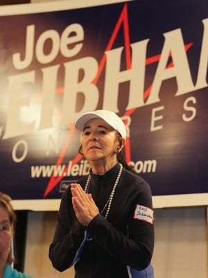 Lois Schmideler prays at about 1 a.m. Wednesday as Joe Leibham supporters maintained hope their candidate could come from behind and erase a Glenn Grothman lead.