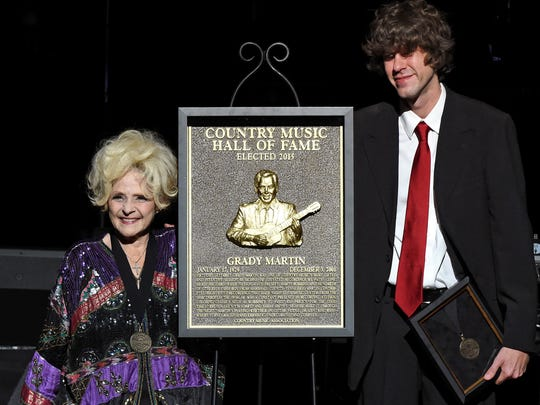 Recording artist Brenda Lee and Joshua Martin (son of inductee Grady Martin) with the plaque honoring Grady Martin during The Country Music Hall of Fame 2015 Medallion Ceremony.
