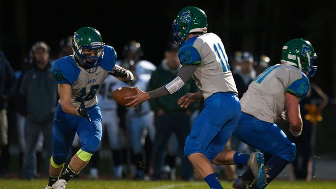 Colchester quarterback Justin Evans (11) hands the ball ff to Dakota Navari (16) during the varsity football game between the Essex Hornets and the Colchester Lakers at Colchester High School on Friday night September 19, 2014 in Colchester.