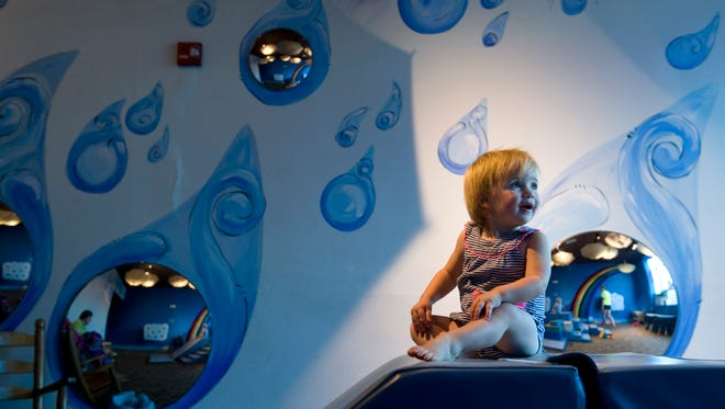 Emma Kirk, 1, of Evansville looks to her mom, Tiffany, before sliding down the padded slide in the Drip Drop Spot at the Children's Museum of Evansville Wednesday afternoon. The museum will be celebrating its 10th birthday the week of Sept. 24-Oct. 1.