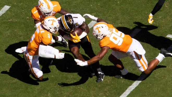 Tennessee defensive back Kenneth George Jr. (5) and linebacker Kivon Bennett (95) tackle Missouri running back Tyler Badie (1) during a Southeastern Conference game Saturday at Neyland Stadium in Knoxville, Tenn.