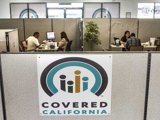 Insurance agents help people sign up for insurance through the Covered California exchange, such as this agency in Huntington Beach in 2016.