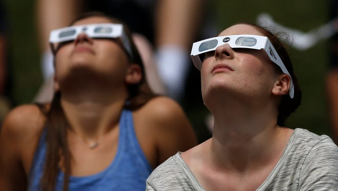 Butler students Alex Idalski, left, and Madison Colbrook join others as they watch the solar eclipse from the Butler campus, outside Holcomb Obseratory, Monday, August 21, 2017.