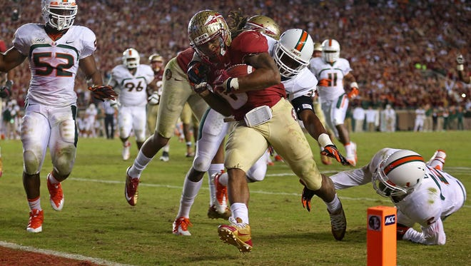 TALLAHASSEE, FL - NOVEMBER 02:  Devonta Freeman #8 of the Florida State Seminoles scores a touchdown during a game against the Miami Hurricanes at Doak Campbell Stadium on November 2, 2013 in Tallahassee, Florida.  (Photo by Mike Ehrmann/Getty Images)