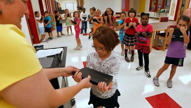 Handing out laptops to second-graders in Round Rock, Texas, in 2010.