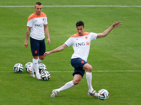 Robin van Persie, right, kicks the ball while Jordy Clasie, left, of the Netherlands waits his turn during a training session in Rio de Janeiro, Brazil, Tuesday, June 10, 2014.  The Netherlands play in group B of the 2014 soccer World Cup. (AP Photo/Wong Maye-E)
