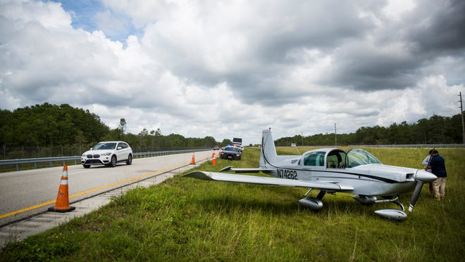 A 1975 Grumman AA-5 Bravo sits on the side of I-75 between mile markers 54 and 50 after an unexpected landing on Monday, June 12, 2017, in Collier County. The pilot was headed to Okeechobee but landed the plane due to power loss.