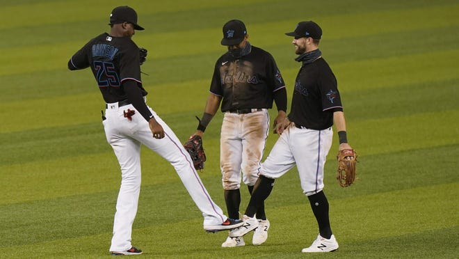 Miami Marlins players Lewis Brinson (25) Magneuris Sierra, center, and Jon Berti celebrate after the Marlins beat the Atlanta Braves 8-2 on Friday night in Miami.