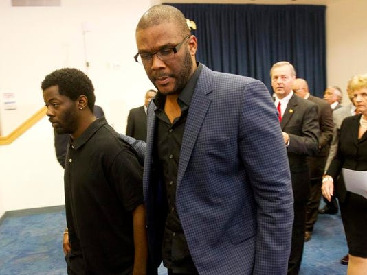 Movie mogul Tyler Perry walks with Anthony Denson Jr., who claimed Thursday that former Collier deputy Steven Calkins chased him