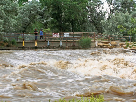 "Jon Austria â "" The Daily Times Onlookers watch as flood waters pass, Thursday, June 11, 2015, along the Animas River near Berg Park in Farmington, N.M."