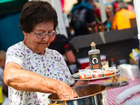 Pat Lawrence, of Hanover, scoops up chili for fans at the Wild West Chili booth during the Hanover Chili Cook Off in 2013. Lawrence has been working at the Wild West booth at the cook-off for 13 years.