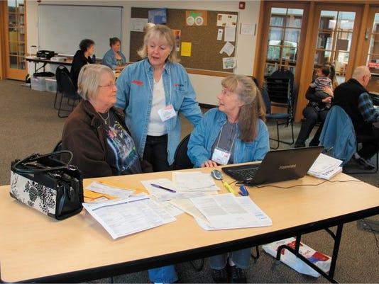 Margaret Hall (left) asks for help filing her tax return Wednesday from as AARP Foundation Tax Aide volunteers Gwen Williams