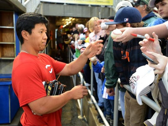 Cincinnati's Ray Chang signs autographs for fans Friday at Blue Wahoos stadium before an exhibition game between the Reds and the Blue Wahoos. The game was canceled due to foul weather.