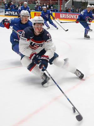 Dylan Larkin of the United States, front, fights for the puck with France''s Jordann Perret during the Hockey World Championships Group B match in St. Petersburg, Russia, Thursday, May 12, 2016.