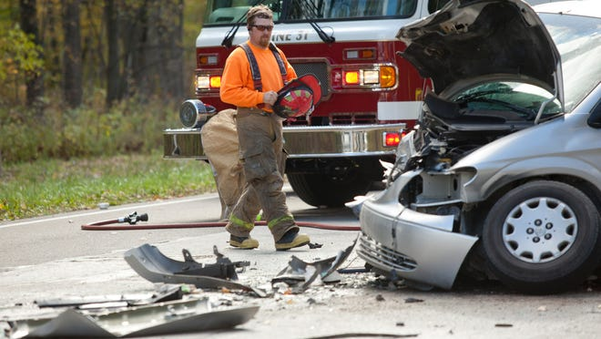 Members of the Burtchville Township Fire Department investigate the scene of a fatal crash between a car and minivan Wednesday in the 7700 block of Lakeshore Road in Burtchville Township.
