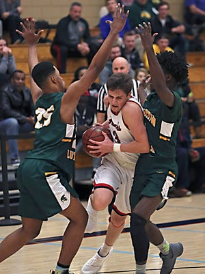 Martin Luther's Shaun Harrison (left) and Ace Evans close in on Racine Prairie's Logan Krekling on Friday night.