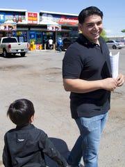 Felix Moran, 25,  walks  with son, Josiah, 4, through