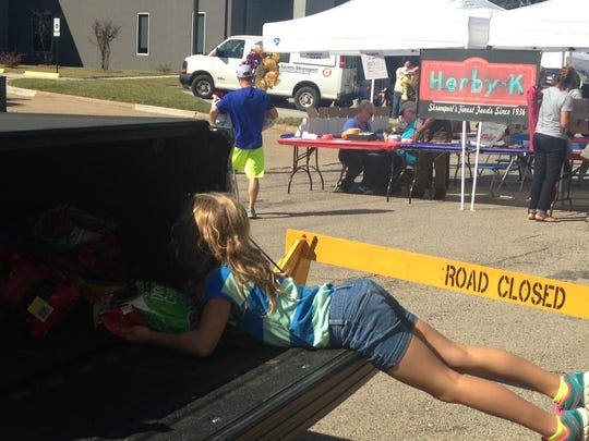 Mallory Benton pulls bags of dog food from her family truck, items she got in lieu of birthday presents to donate to Pet Savers at the 2014 Herby-K's block party.