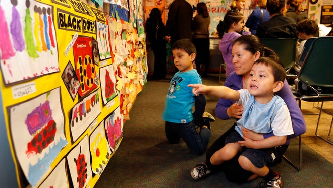 A Spring Valley mom and her two boys looks at artwork during an East Ramapo Universal Pre-Kindergarten art festival in May.
