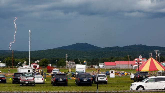 A storm moves in Tuesday Aug. 4, 2015, as investigators inspect the site of a circus tent that collapsed Monday during a show by the Walker Brothers International Circus at the Lancaster Fair grounds in Lancaster, N.H.  A quick moving storm with 60 mph winds hit the tent shortly after the show started killing a father and daughter.  (AP Photo/Jim Cole)