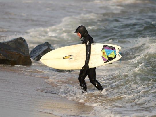 With her surfboard in hand, Laurel Harrington emerges
