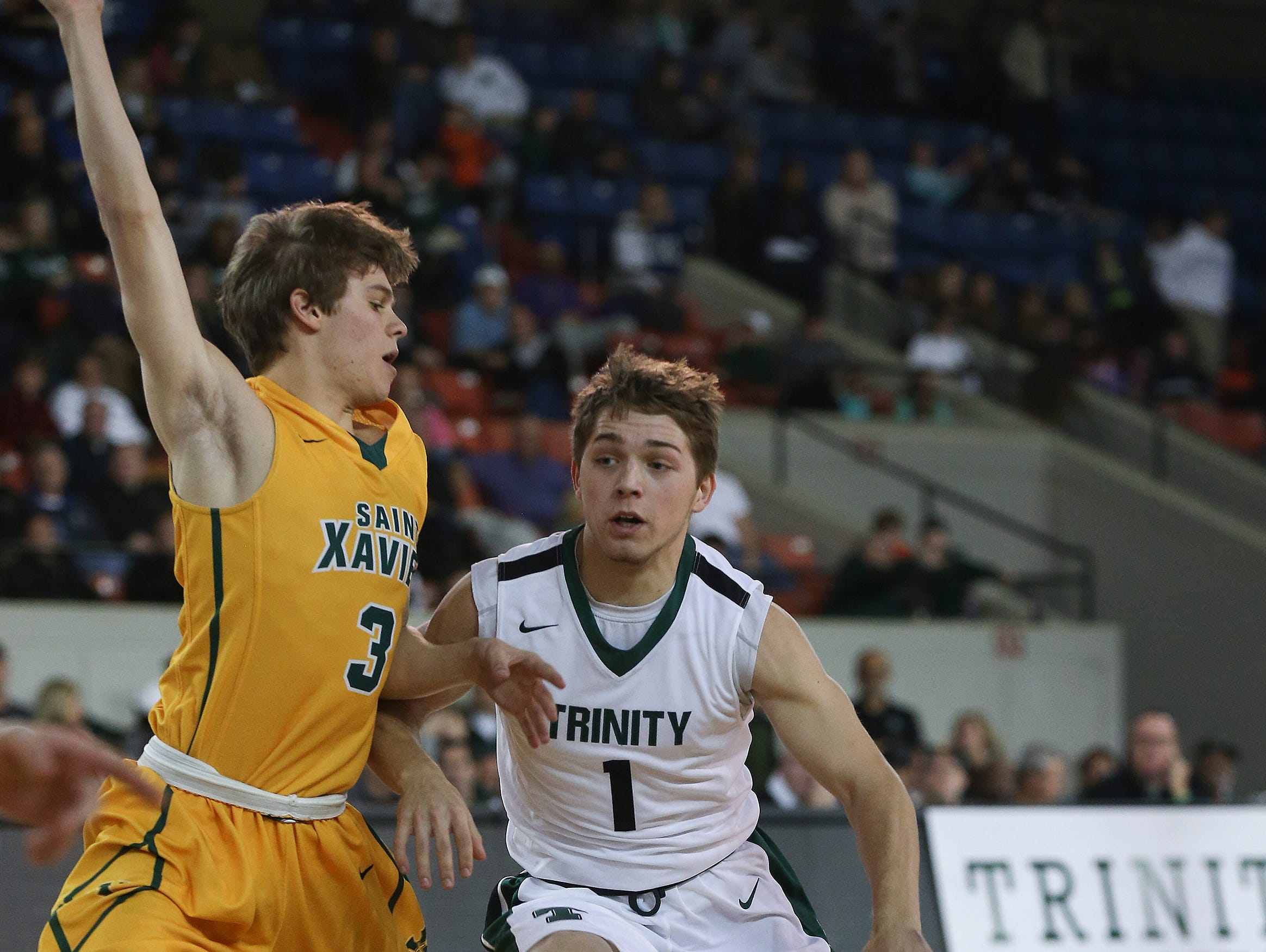 Trinity's Jacob King (1) drives against St. X's Cameron McDonogh (3) during their game at Broadbent Arena. Jan. 6, 2017