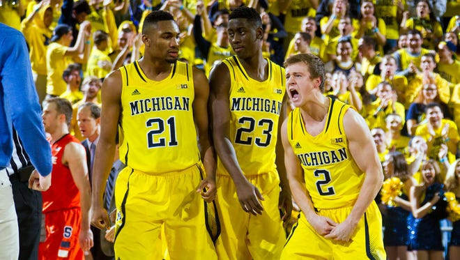 Michigan guard Spike Albrecht, right, celebrates with teammate Zak Irvin, left, during a time-out at Crisler Center in Ann Arbor on Dec. 2, 2014.