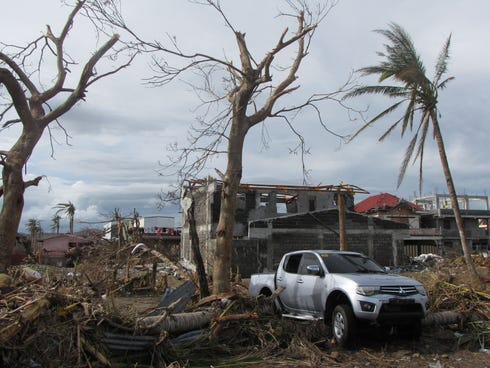 The pick-up truck in which two infants, five children and two adults drowned Friday, lies amid a typhoon damaged village near the seaside town of Palo in Leyte province, central Philippines.