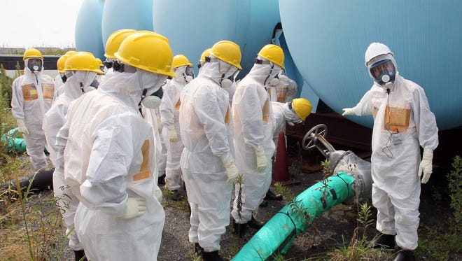 In this September 2013 photo, members of a prefectural committee on the Fukushima Dai-ichi nuclear plant inspect tanks holding toxic water at the tsunami-crippled plant in Okuma town, Fukushima prefecture, Japan.